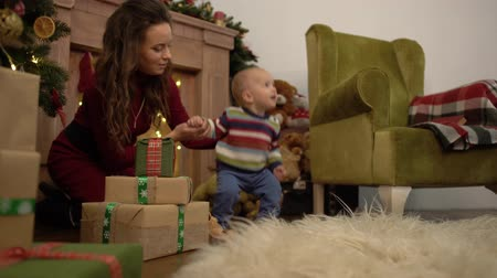 puericultura : Cute joyful cheerful mother and baby spend their leisure time next to the Christmas tree at home. Stock Footage