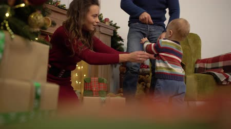Çocuk bakımı : Cute joyful cheerful mother, dad and baby spend their leisure time next to the Christmas tree at home. Stok Video