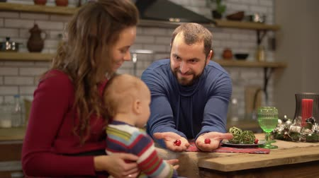 choise : Mother, father and a baby have a fun in modern kitchen. Dad and mom playing with child, man shows two fists with hiden candies proposing to choose one. Happy family spend time together
