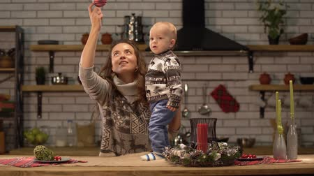 Çocuk bakımı : Pretty young woman lifts up the baby in her arms standing in modern kitchen showing to son bright red Christmas tree toy hanging from the ceiling. Happy family concept