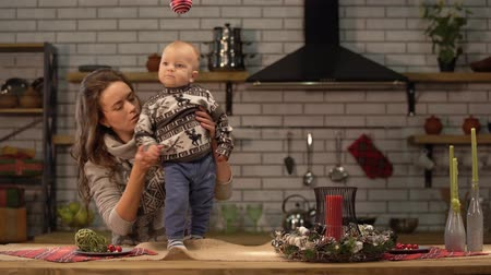 first person : Pretty young woman and cute baby in her arms standing in modern kitchen. Happy family concept. Stock Footage