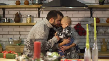 dom : Bearded father in warm sweater playing with baby little son in mother arms in the kitchen. Man gives pepper pot to child and he shakes it. Happy friendly family spend time together