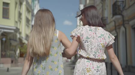 シック : Back view of two walking women with shopping bags. Young girls wearing stylish summer dresses enjoying with spending time. Shopping lifestyle concept. Slow motion.