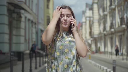 šik : Happy young woman talking by cell phone walking through city street. Fun girl wearing stylish summer dress enjoying outdoors. Slow motion.
