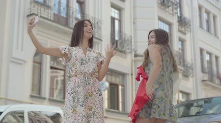 потребитель : Two happy girlfriends after shopping with shopping bags taking selfie on cellphone with new clothes outdoors. Leisure of happy girls. Carefree ladies walking through city street.