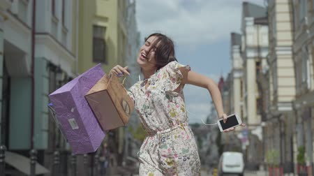 ubrania : Cute cheerful young woman with shopping bags. Girl with headphones and cell phone listens to music while dancing through city street. Young fun girl wearing stylish summer dress enjoying outdoors.