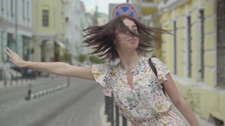 シック : Pretty carefree young woman wearing summer dress with shopping bags in hands trying to catch the taxi in the street of an old european city. Leisure of happy girl. Shopping time, vacation 動画素材