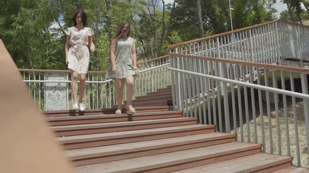 conserva : Two attractive girls wearing summer dresses running down the stairs in the city park. Carefree girlfriends having fun outdoors. Summertime leisure of girlfriends.