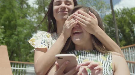 conserva : Adorable young girl sitting in the foreground texting on the cellphone. Carefree friend runs up behind her and closes her friends eyes with her hands, girlfriends hugging. Friendship concept. Summertime leisure Stock Footage