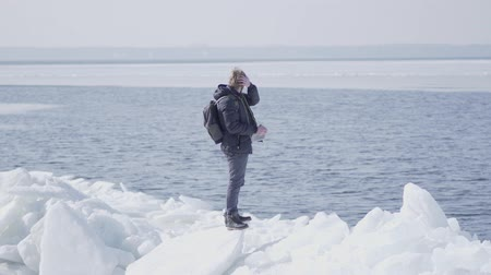 icy : The man wearing a warm coat standing on the glacier straightens his hair and looking away. Amazing nature of a snowy lake and glacier. The man standing on the ice