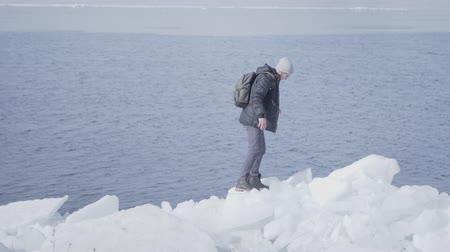 icy : Young blond bearded handsome man wearing warm jacket, hat and boots climbing the glacier, walking on the edge. Amazing nature of a snowy North or South Pole. The brave polar explorer on the block of ice Stock Footage