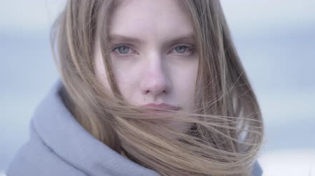 radiante : Close-up of beautiful young blond woman with long hair and blue eyes looking in the camera. Attractive woman of Scandinavian appearance Stock Footage