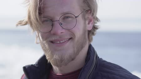 beardie : Portrait of handsome bearded man in glasses with sticking blond hair looking in the camera smiling close up. Positive guy, front view