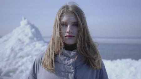 icy : Pretty woman with long blond hair in warm coat looking in the camera standing on the glacier. Amazing view of a snowy North or South Pole on the background. Camera moving around Stock Footage