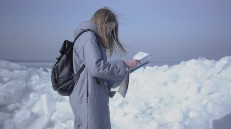 Антарктика : Attractive blond woman with backpack checking the map in front of ice at the North or South pole. Tourist travels in the winter. The girl is lost and wants to find a way Стоковые видеозаписи
