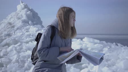 icy : Portrait of young blond pretty woman in warm jacket standing on the glacier checking with the map. Amazing nature of snowy North or South Pole. The tourist in front of the ice blocks. Lady is lost