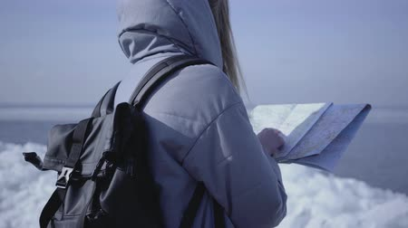 icy : Back view of young blond woman in warm jacket with backpack standing on the glacier checking with the map. Amazing nature of snowy North or South Pole. The tourist in front of the ice blocks Stock Footage