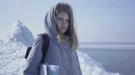 don : Portrait of young blond pretty woman in warm jacket standing on the glacier with the map in hands, looking in camera. The tourist in front of the ice blocks. Camera moving left