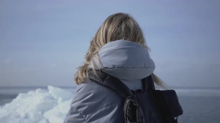 geleira : The blond attractive woman calling to her friend by her cellphone standing on an ice floe. The tourist in front of the ice blocks and sea