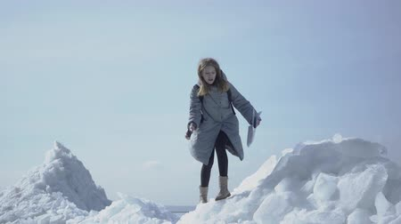 iceberg : Portrait of cute woman in warm jacket walking on the glacier, holding her cellphone in raised hand, trying to find mobile network. The tourist in front of the ice blocks and sea