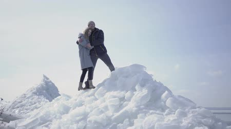 hayran olmak : Beautiful blond couple pointing away hugging each other. The bearded man in glasses and attractive woman admiring nature in the winter. Tourists travel together