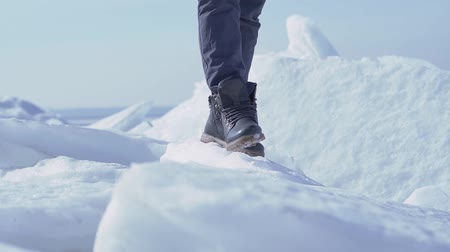 climbed : Unrecognized man climbed to the top of ice glacier in cold winter weather. Slow motion. Stock Footage