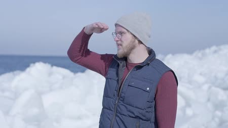 Антарктика : Young handsome man geologist focused on something near cold ice snowing glacier behind the winter sea. Slow motion Стоковые видеозаписи