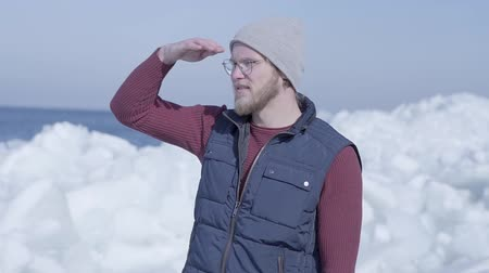 Антарктика : Young handsome man tourist focused on something near cold ice snowing glacier behind the winter sea. Slow motion