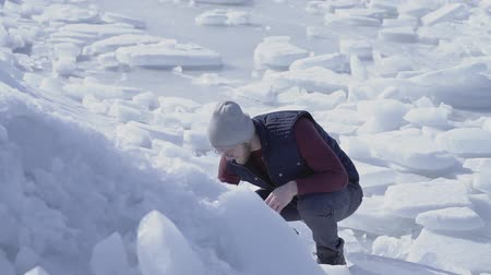 antártica : Young handsome man geologist searched something in cold ice snowing glacier behind the winter sea. Slow motion Stock Footage