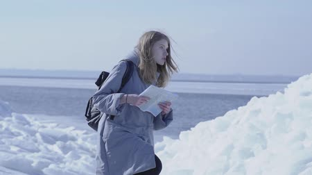 turisták : Young blond pretty woman wearing warm jacket standing on the glacier checking with the map. Amazing nature of snowy North or South Pole. The tourist in front of the ice blocks. Slow motion.