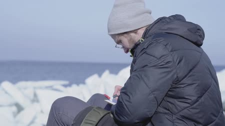 Антарктика : Handsome blond bearded man sitting among the ices writing his observations in a notebook. Polar explorer on glacier. Slow motion.