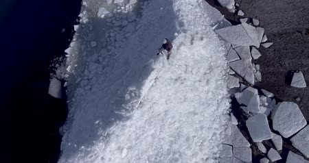 Антарктика : Aerial dron view of young active happy man staying on the ice glaciers near coastline of winter sea. Drone view.