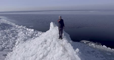 iceberg : Aerial dron view of young active happy man staying on the ice glaciers near coastline of winter sea. Drone flies into the hands of a guy. Stock Footage