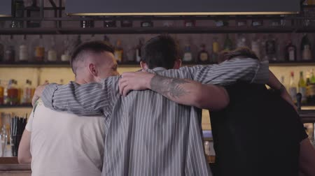seçkinler : Back view of two men sitting at the bar counter. Third guy joining the company, mates hugging. Relaxed male friends chilling together drinking elite alcohol. Day off