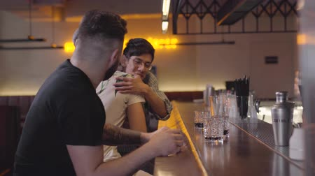 seçkinler : Two adult men sitting at the bar counter, third guy joining the company, mates hugging and giving high five. Relaxed male friends chilling together drinking elite alcohol. Day off Stok Video