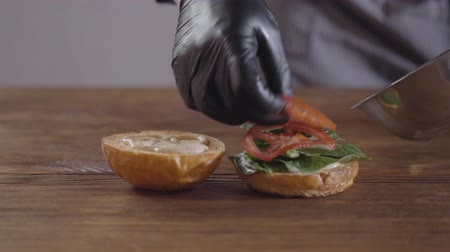 top chef : Hands of the chef in black kitchen gloves making burger close-up. The cook putting tomato slices on basil leaves on the one piece of a hamburger bun. Tasty food preparation