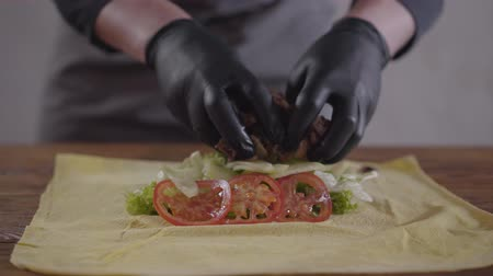 pronto a comer : Hands of the chef in black kitchen gloves making shawarma close-up. The cook putting meat, tomatoes and onion on the pita close-up. Tasty arab snack preparation Stock Footage