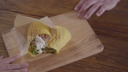türkische küche : Tasty shawarma with sauce lying on the wooden board. Male and female hands pulling to themselves board with food. Tasty arab snack serving. Top view Videos