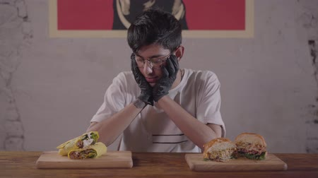 shoarma : Young skinny man in glasses and black gloves sitting at the table in front of appetizing burger and shawarma choosing what to eat first. The guy dining in the modern restaurant Stockvideo