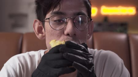 mouth watering : Close-up portrait of cute skinny young man in glasses and black gloves eating tasty shawarma. The man enjoying mouth-watering fast food in the modern restaurant.