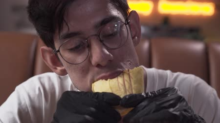 pan pita : Close-up portrait of a skinny young man in glasses and black gloves eating tasty shawarma. The man enjoying mouth-watering fast food in the modern restaurant
