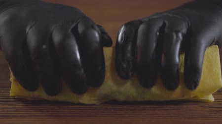 mouth watering : Close-up hands of the skill chef in black rubber gloves making shawarma. The cook rolling shaurma in the pita on the wooden board. Tasty snack preparation. Slow motion. Stock Footage
