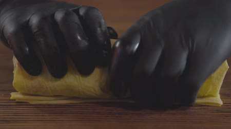 shoarma : Close-up hands of the skill chef in black rubber gloves making shawarma. The cook rolling shaurma in the pita on the wooden board. Tasty snack preparation. Slow motion. Stockvideo