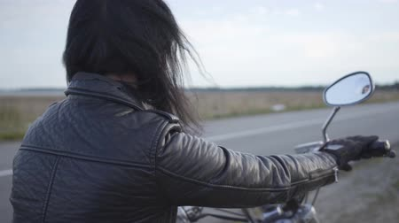 runaway : Back view of unrecognizable girl in old leather jacket sitting on the motorcycle looking away. Hobby, traveling and active lifestyle. Female biker outdoors. Leisure and travel by motorcycle