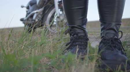 runaway : Legs of an unrecognized biker in black leather pants and sneakers standing on the grass in the field. Motorcyclist on the background of a motorcycle outdoors. Hobby, traveling and active lifestyle.