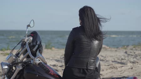 runaway : Back view of the pretty caucasian girl sitting on the motorcycle looking away on the riverbank. Hobby, traveling and active lifestyle. Leisure and travel by motorbike. Stock Footage