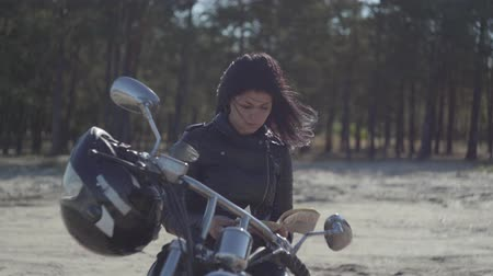runaway : Back view of the pretty caucasian girl in a black leather jacket sitting on the motorcycle reading book. Hobby, traveling and active lifestyle. Leisure and travel by motorbike. Stock Footage