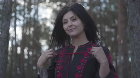 umutlu : Portrait of attractive young woman tying the lace on a black and red dress standing under the trees in the pine forest. The girl looking into the camera smiling. Connection with nature