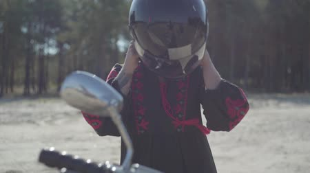persons : Caucasian girl sits on her motorcycle and wears a helmet. Skill woman in a black leather dress riding a classic motorbike. Hobby, traveling. Leisure and travel by motorcycle. Slow motion.