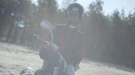 rebelião : Front view of the girl in the helmet standing at the motorcycle in front of pine forest in sunlight. Hobby, traveling and active lifestyle. Attractive female biker outdoors on her motorbike. Slow motion. Stock Footage